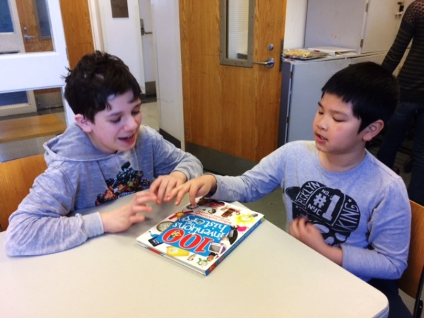 Two boys with autism read a book together at Kids' Connection Corner, a JF&CS program for kids with autism