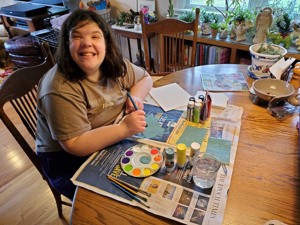 A CHAI Works participant painting at home.