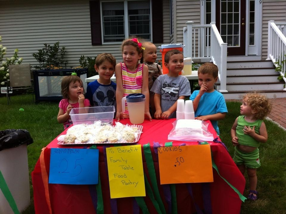 A group of kids fundraising for Family Table with a lemonade stand.