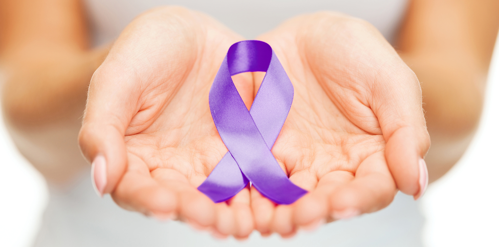 A woman holding a purple ribbon for Domestic Violence Awareness Month.