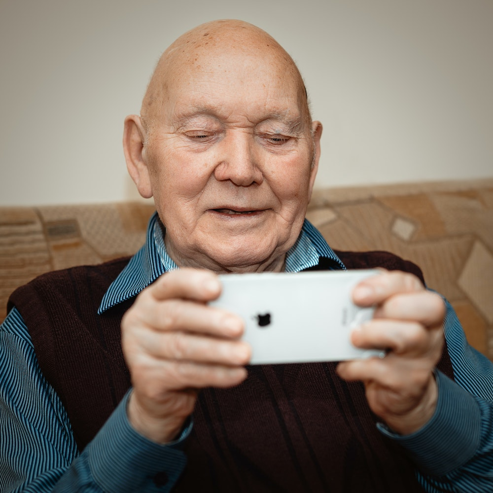 An older man video chatting on a smartphone.